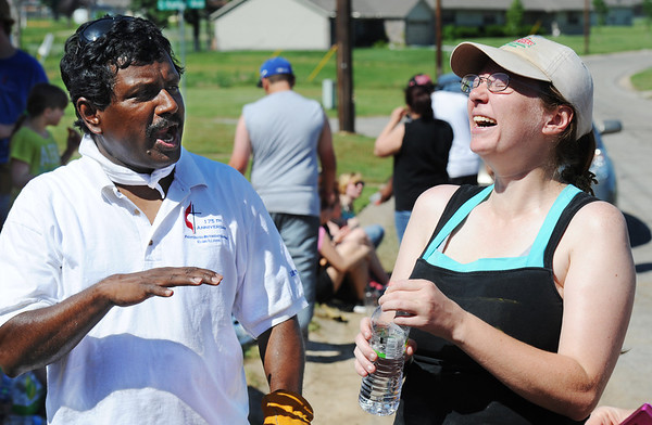Globe/T. Rob Brown<br /> The Rev. Robert Sathuri (left) from First United Methodist Church in Elgin, Ill., tells a funny story to Joplin home owner Emily Morrison Monday morning, June 10, 2013, as they take a water break from working on her home. The church youth group is working in conjunction with Rebuild Joplin.