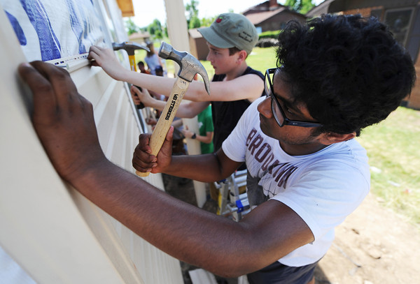 Globe/T. Rob Brown Kenny Chinnam, 13, (right) and Glenn Johnston, 16, both members of the First United Methodist Church youth group from Elgin, Ill., install siding on a Rebuild Joplin home being built for Emily Morrison, Thursday morning, June 13, 2013.