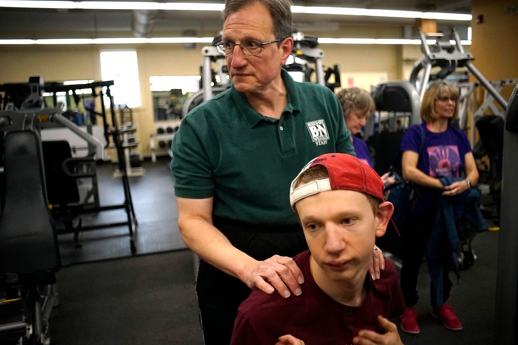 . Glenn McBurney comforts his son Elijah at Berkshire Nautilus (where Glenn works) during Elijah\'s workout. Elijah is 20 years old and has a rare, degenerative brain disease called BPAN. Thursday, October 27, 2016. Ben Garver � THe Berkshire Eagle