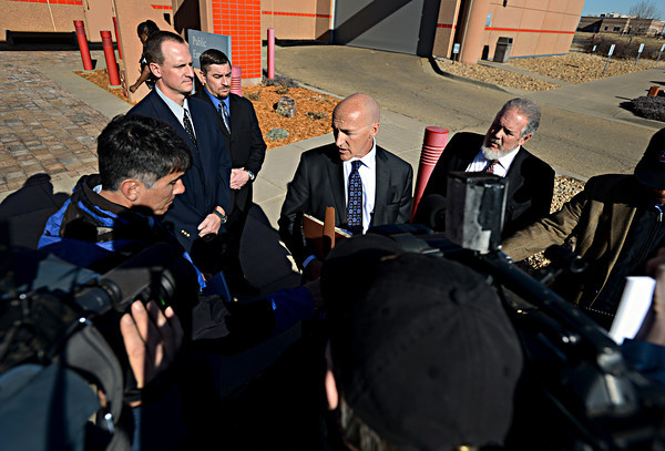 Former Boulder Police Officers Brent Curnow, top left, and Samuel Carter listen as their lawyers, Patrick Mulligan, center, and Marc Colin give a statement outside the Boulder County Jail after the filing of charges in the case of the Mapleton Hill elk shooting in Boulder on Thursday, Feb. 7, 2013. <br /> (Greg Lindstrom/Times-Call)