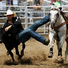 JAY YOUNG | THE GOSHEN NEWS<br /> Cord Barricklow, of Lebanon, leaps off his horse to grab a steer by its horns as he competes in the steer wrestling event at the Friday afternoon rodeo during the Elkhart County 4-H Fair.