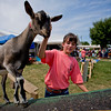 JAY YOUNG | THE GOSHEN NEWS<br /> Ten-year-old Madilyn Zimmer, of Goshen, leads her goat, named Snickers, over the seesaw as she practices for the goat agility skills contest Wednesday afternoon at the Elkhart County 4-H Fair.