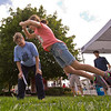 JAY YOUNG | THE GOSHEN NEWS<br /> Wendie House, left, of Elkhart, watches as 9-year-old Miley Ragsdale, of Middlebury, takes a giant leap forward while trying her hand at the long jump skills station during Disabilities Awareness Day at the Elkhart County 4-H Fair Monday afternoon.