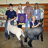 JOHN KLINE | THE GOSHEN NEWS<br /> Grand Champion Lamb Pen of 2 winner Alexis Kingen, second from right, kneeling, shows off her winning lambs with the assistance of fellow 4-Her Austin Bernicky, left, and buyers, from left, Cathy Hoogenboom, Tim Hoogenboom and Shelly Steury, Michiana Auto Sport, during the Elkhart County 4-H Lamb Auction Friday afternoon.