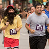 JAY YOUNG | THE GOSHEN NEWS<br /> Dressed as Forrest Gump, {749} runs next to (831) down Main Street in downtown Goshen as the two compete in the annual Elkhart County 4-H Fair road race Sunday afternoon.