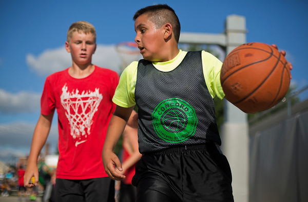 JAY YOUNG   THE GOSHEN NEWS<br /> Ten-year-old Pedro Celis looks over his shoulder at defender Ben Keil, 12, as they compete in the three-on-three basketball tournament Monday evening at the Elkhart County 4-H Fair.