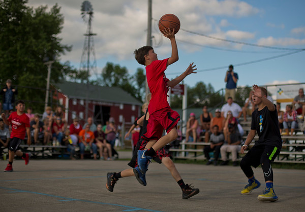 JAY YOUNG   THE GOSHEN NEWS<br /> Nine-year-old Levi Sawatzky hangs in the air to get off a shot over defender Tre Willard, 10, as they compete in the three-on-three basketball tournament Monday evening at the Elkhart County 4-H Fair.