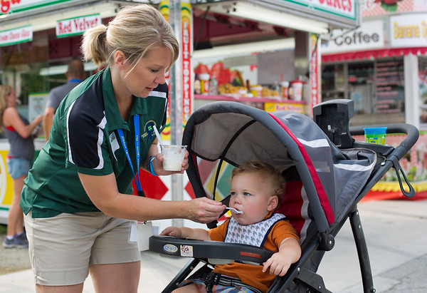 JAY YOUNG | THE GOSHEN NEWS<br /> Monica Gould gives her 1-year-old son Nolan some ice cream while they attend Taste of the Fair Thursday evening at the fairgrounds in Goshen.