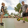 JAY YOUNG | THE GOSHEN NEWS<br /> Nine-year-old Lilly Giudice, of Mishawaka, watches while Michael Paff, of Huntington, dribbles the ball while trying his hand at a basketball skills event during Disabilities Awareness Day at the Elkhart County 4-H Fair Monday morning.