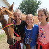 JOHN KLINE | THE GOSHEN NEWS<br /> Gaby Gates, 11, Sabrina Miller, 11, and Kendal Jones, 11, with horse, Emmy
