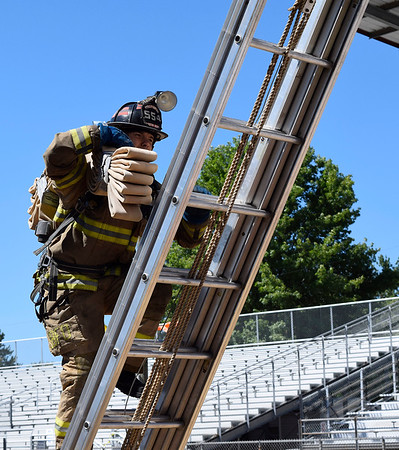 CHRISTINA CLARK | THE GOSHEN NEWS Josh Comeau of South Bend Fire Department carries a high-rise pack up fifteen feet on Saturday.
