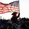 BEN MIKESELL | THE GOSHEN NEWS<br /> A woman carrying an American flag rides her horse away from the arena after the national anthem during Friday night's rodeo at the Elkhart County 4-H Fair.