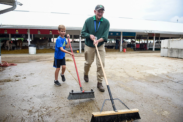 BEN MIKESELL | THE GOSHEN NEWS<br /> Wyatt Rossi, 8, Goshen, helps 2016 Fair President Bob Zell of Nappanee keep the ground clean near the dairy feeder calf club at the Elkhart County 4-H Fair.