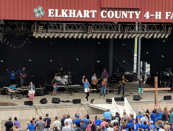 SHEILA SELMAN | THE GOSHEN NEWS<br /> Elkhart County 4-H fairgoers worship Sunday morning at the grandstands. The morning service was led by Pastor Jim Brown of Grace Community Church and its worship band headed by worship Pastor Jeremy Byng. Thousands attended the service.