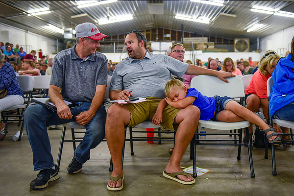 "BEN MIKESELL | THE GOSHEN NEWS<br /> Ryder Lambright, 4, right, gets a much needed rest while his dad Brian, of Shipshewana, conducts business during the swine auction Friday afternoon at the Elkhart County 4-H Fair. For photos of the Grand Champion livestock exhibits and a complete list of buyers, go online to  <a href=""http://www.goshennews.com"">http://www.goshennews.com</a> or pick up a copy of the post-fair tab in the Aug. 8 edition of The Goshen News."