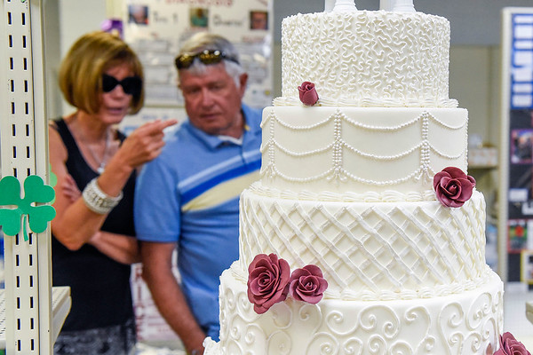 BEN MIKESELL | THE GOSHEN NEWS<br /> Doug and Risa Young of Bourbon examine a cake made by Ainslee Zou, which won reserve champion, on display Thursday in the Exhibit Hall at the Elkhart County 4-H Fair.