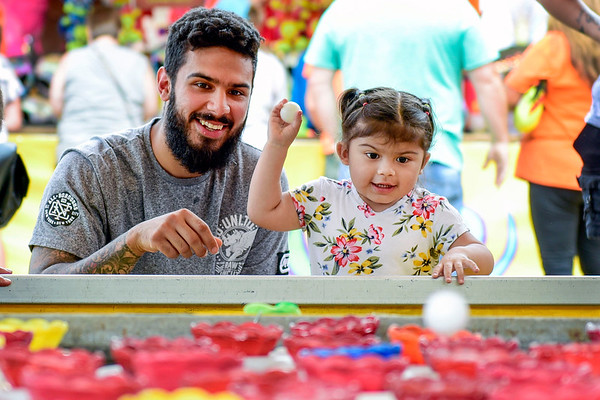 BEN MIKESELL | THE GOSHEN NEWS<br /> Javier Mingucha, of Goshen, watches his daughter Scarlett, attempt a throw in the buoy ball game Saturday afternoon at the Elkhart County 4-H Fair.