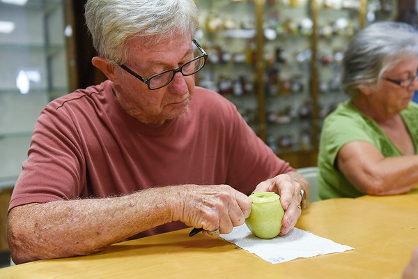 BEN MIKESELL | THE GOSHEN NEWS<br /> Ned Miller, Goshen, concentrates on peeling his apple during Tuesday morning's apple peel contest at the Home and Family Arts Building. Miller's peel measured at 50 inches.