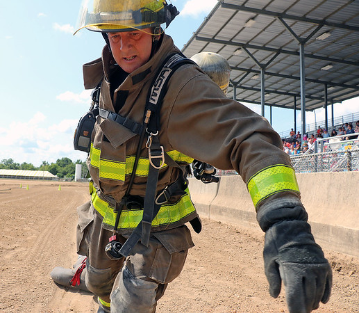 AIMEE AMBROSE | THE GOSHEN NEWS<br /> <br /> Lavern Hurst, with the Wakarusa Volunteer Fire Department,  drags a 165-pound dummy to the finish line during the firefighter challenge at the Elkhart County 4-H Fair Saturday. Hurst was one of seven firefighters to compete in the second-annual event, which involved a course of challenges designed to resemble real-world firefighting situations.