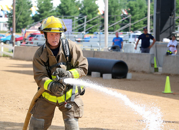 AIMEE AMBROSE | THE GOSHEN NEWS<br /> <br /> Lavern Hurst, with the Wakarusa Volunteer Fire Department, sprays water from a fire hose at a target during the firefighter challenge at the Elkhart County 4-H Fair Saturday. Hurst was one of seven firefighters to compete in the second-annual event, which involved a course of challenges designed to resemble real-world firefighting situations.