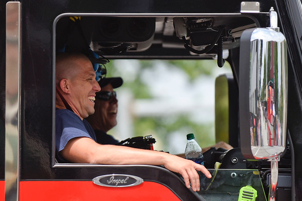 BEN MIKESELL | THE GOSHEN NEWS<br /> Goshen Fire Department fire fighters laugh from their cab as they drive down Lincoln Avenue during the 2018 4-H Fair Parade Sunday in downtown Goshen.