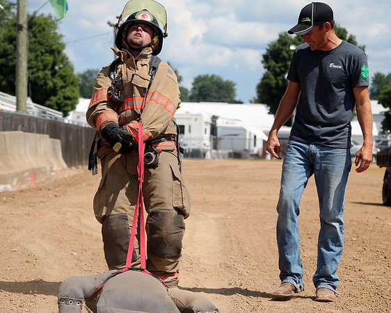 AIMEE AMBROSE | THE GOSHEN NEWS<br /> <br /> P.J. Metzler, with the Benton Township Volunteer Fire Department,  drags a 165-pound dummy to the finish line during the firefighter challenge at the Elkhart County 4-H Fair Saturday. Metzler was one of seven firefighters to compete in the second-annual event, which involved a course of challenges designed to resemble real-world firefighting situations.