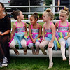 BEN MIKESELL | THE GOSHEN NEWS<br /> DES Dance members, from left, Maggie West, 15, of Goshen, Bailey Miller, 6, of Millersburg, Aryanna Burt, 6, of Goshen, and sisters Eloise and Evelyn Garner, both 5, of New Paris, sit on the bleachers before performing for National Dance Day Saturday at Heritage Park Stage.