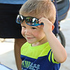 LEANDRA BEABOUT | THE GOSHEN NEWS<br /> Oliver Mueller, 2, Goshen, removes his sunglasses to see the demonstration at a booth during Kid's Day at the Elkhart County 4-H Fair.