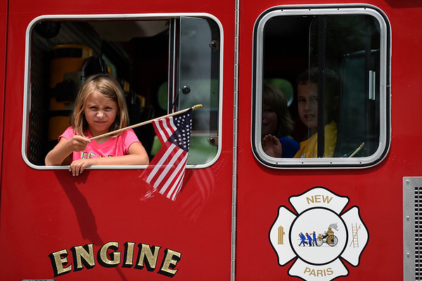 BEN MIKESELL | THE GOSHEN NEWS<br /> A girl waves an American flag out the window of a New Paris Fire Engine during the 2018 4-H Fair Parade Sunday in downtown Goshen.