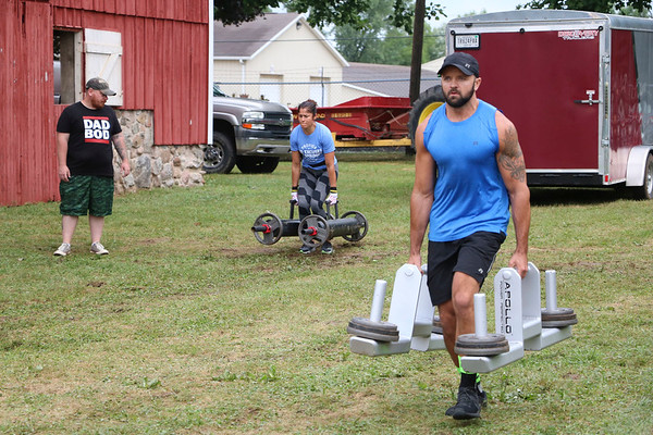 LIZ RIETH   THE GOSHEN NEWS Bertha Luna, Elkhart, and Dustin Snider, New Paris, compete in the farmer's walk event in the Elkhart County 4-H Fair Strongman Competition Saturday.