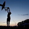 BEN MIKESELL | THE GOSHEN NEWS<br /> Olazarus Miller goes up for a dunk during the dunk contest Thursday at the Elkhart County 4-H Fair. Miller won the dunk contest by a few points, beating recent Goshen High School graudate Will Line.