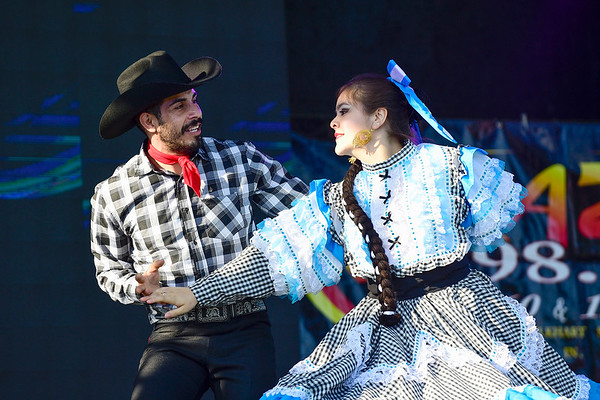 BEN MIKESELL | THE GOSHEN NEWS<br /> Eric Zaragoza of Mexico dances with Mariana Rangel, 15, of South Bend during the opening act of Friday's Latino Night at the Heritage Park Stage.