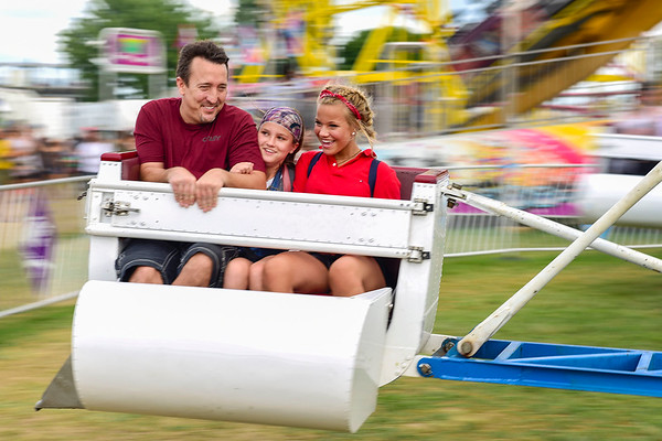 BEN MIKESELL | THE GOSHEN NEWS<br /> Shane Kibbe, Elkhart, rides The Scrambler with Mia, 12, and Maddie Kibbe, 15, Saturday afternoon at the Elkhart County 4-H Fair.