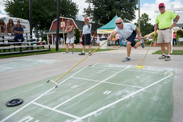BEN MIKESELL | THE GOSHEN NEWS<br /> Terry Wingard of Middlebury, middle, faces off against Dean Wass of Monroeville during a shuffleboard tournament Tuesday afternoon at Heritage Park during the Elkhart County 4-H Fair.