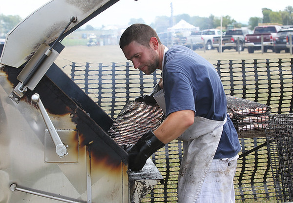 Justin Hilimire of Ace Automatics makes some barbecue chicken for the Lochland School food tent.