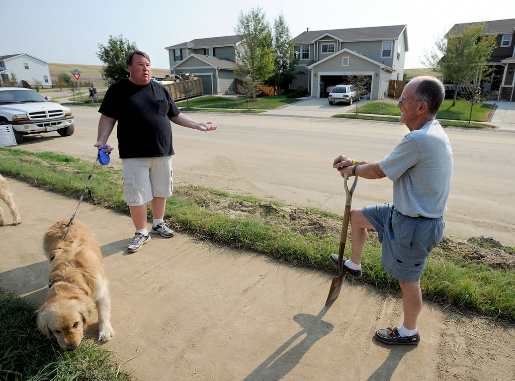 . Kyle Martz, left, talks to neighbor, Ray Franks, who is cleaning the mud from the sidewalks. The Grandview neighborhood of Erie is up in arms about the town\'s apparent unwillingness to do anything to shore up their ditches and retaining walls, which spill mud and water into the neighborhood during storms. Neighbors say the town insists that it is the homeowners associations responsibility to take care of these problems, but the neighbors think the town should do it. Cliff Grassmick  / August 16, 2013