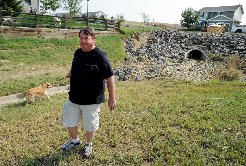 . Kyle Martz shows one of the drainage areas that was overwhelmed by the mud, rocks and flood water. The Grandview neighborhood of Erie is up in arms about the town\'s apparent unwillingness to do anything to shore up their ditches and retaining walls, which spill mud and water into the neighborhood during storms. Neighbors say the town insists that it is the homeowners associations responsibility to take care of these problems, but the neighbors think the town should do it. Cliff Grassmick  / August 16, 2013