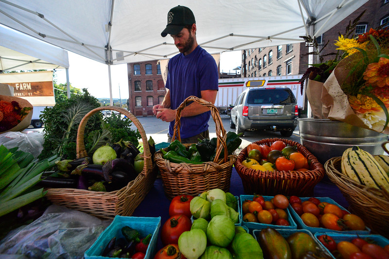 KRISTOPHER RADDER - BRATTLEBORO REFORMER<br /> Andy Lougheny, of Tapalou Guild, prepares some garlic before the start of the evening farmers market in Brattleboro on Tuesday, Sept. 19, 2017.