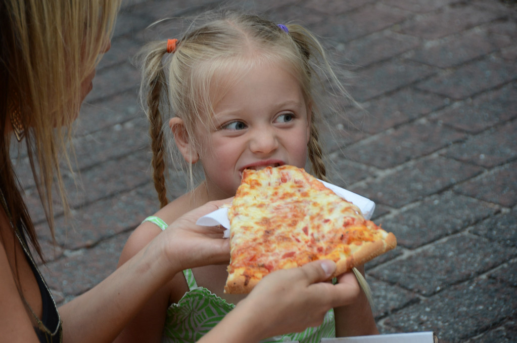 . Crystal Casal holds a piece of pizza from Liberty Pizza for her daughter Londyn, 6, to eat, during Third Thursday festivities on July, 17, 2014. Gillian Jones / Berkshire Eagle Staff / photos.berkshireeagle.com