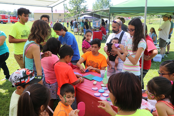 GEOFF LESAR | THE GOSHEN NEWS<br /> <br /> Volunteer José Chiquito,18, Goshen, instructs a group of children on how to make paper cranes Saturday at the Maple City Cultural Festival.