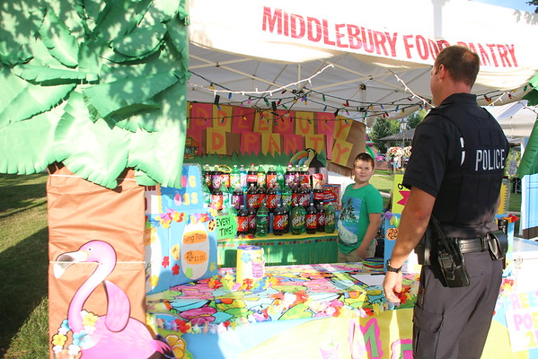 KRIS MUELLER | THE GOSHEN NEWS<br /> Officer Jeff Wodtkey takes his turn at the Middlebury Food Pantry's ring toss booth, as Alex Vorobyov encourages him at the Middlebury Summer Festival. All proceeds benefited the Food Pantry