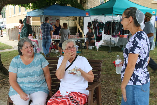 KRIS MUELLER | THE GOSHEN NEWS<br /> Elnora Miller, Gloria Shetler and Martha Mullet catch up on family and friends Friday night at the Middlebury Summer Festival.