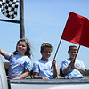 HALEY WARD | THE GOSHEN NEWS<br /> First place finishers Jaidyn Whipple, Kameron Kast and Collin Vidmar ride back to their families in the back of a truck during the Elkhart County Soap Box Derby on Saturday at the Elkhart County Fairgrounds. It is an tradition that the winners of the three divisions ride back in the truck while waving the flags.