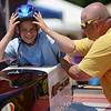 HALEY WARD | THE GOSHEN NEWS<br /> Mark Scholl helps his son Tanner, 9, in his car during the Elkhart County Soap Box Derby on Saturday at the Elkhart County Fairgrounds. He finished second in the Stock division.