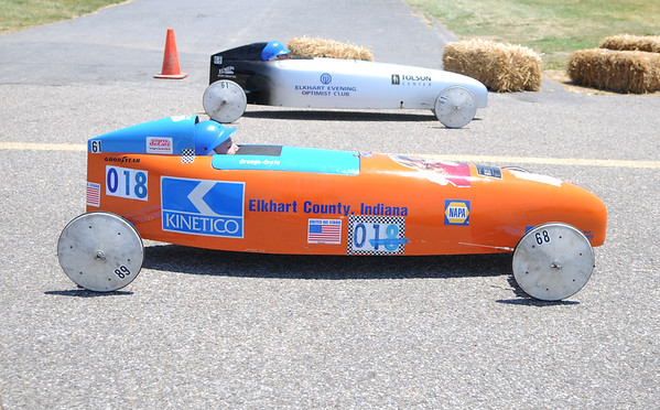 HALEY WARD | THE GOSHEN NEWS<br /> Chad Kennedy in the orange car and Collin Vidmar in the silver car race in the championship of the Masters division in the Elkhart County Soap Box Derby on Saturday at the Elkhart County Fairgrounds. Vidmar finished first.