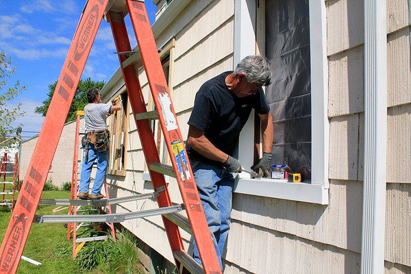 Roger Schneider | The Goshen News<br /> Alfonso Jimenez installs window flashing during Help-A-House Saturday. Jimenez was working on the home of Doug Cripe on South 11th St. in Goshen.