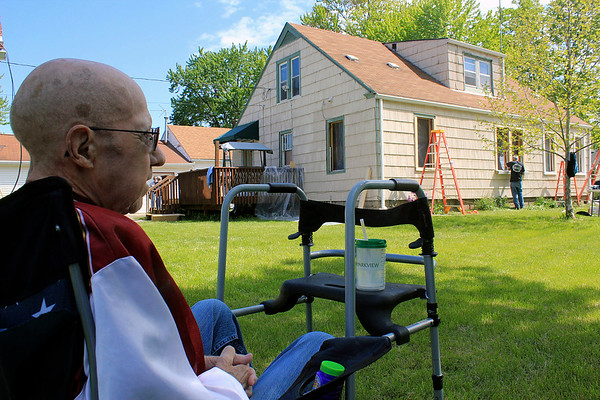 Roger Schneider | The Goshen News<br /> Doug Cripe watches Help-A-House volunteers install new windows at his South 11th Street home in Goshen.