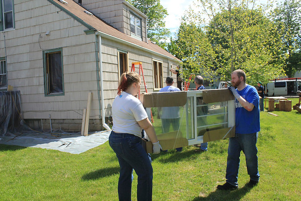 Roger Schneider | The Goshen News<br /> Abby Nafziger and her husband Alex Peterson carry a window at the home of Doug Cripe during Help-A-House Saturday.
