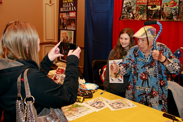 Brian Sapp | The Goshen News<br /> Annastasia McPherson of South Bend takes a picture of her daughter Akira with Allen<br /> Bellman who worked on Captain America comic backgrounds.