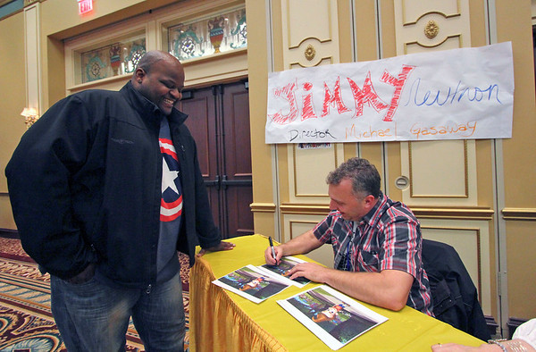 Roger Schneider | The Goshen News<br /> Mo Green of South Bend watches Michael Gasaway sign a picture of Jimmy Neutron at the Hall of Heroes Comic Con Saturday. Gasaway was director of the computer animated TV series.